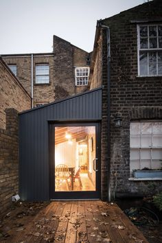 YARD Architects side extension with painted timber cladding and a large pivot door onto garden