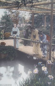 Geisha's look at their reflections in a landscaped garden pond, 1910 by Tamamura Kozaburo