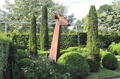 Heerenhof Garden or H House   corten giraffe flanked by the Upright Irish Yew (Taxus baccata 'Fastigiata)