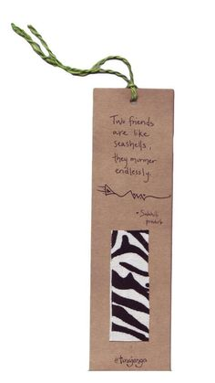 """Kitenge Fair Trade African Proverb Friends Bookmark  Kenya - This bookmark is perfect for holding your spot in your favorite book, and makes a great gift for teachers. Bookmark made of recycled paper and up-cycled kitenge fabric swatches. Fabric colors and patterns vary. Swahili proverb reads: """"Two friends are like seashells; they murmur endlessly"""" A fair trade product from Kenya. This bookmark was made by men of different ethnic groups who are working together to build strong homes…"""