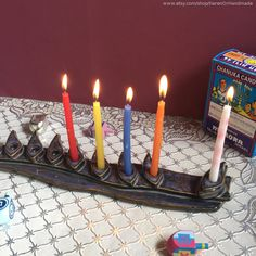 I fired this menorah (chanukiah) with a lead-free green glaze and reddish brown stain. Using high-fire porcelain in the hand-built method, I created these 2 narrow slabs as the base and cut-out leaves as the candle cup holders in the menorah and I stamped the base with a tree of life stamp.  I fired it to bisque and after taking it out the kiln I glazed it with this beautiful lead free purple plum  glaze and high fired it again. Ceramic menorahs by KerenOrHandmade on Etsy