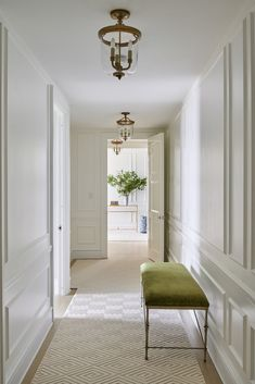 A custom runner by STARK Carpet and fixtures from Circa Lighting make for a traditional, New England feel in this hallway.
