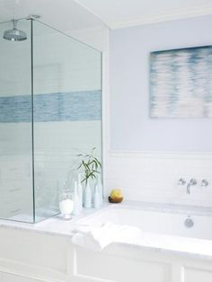 Meghan gave the white shower a seaside spin with a 12-inch swath of blue mosaic glass tile. Coastal art like this rippled-water canvas print is an easy way to beach up a bathroom.