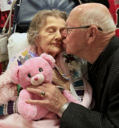 Ginny Griffin, of Akron, (left) gets a kiss from her husband Jim Griffin as she holds her new teddy bear with a recording of Jim's voice at Build-A-Bear Workshop in Summit Mall Thursday in Fairlawn. Ginny has dementia and the bear with Jim's voice is meant to comfort her at her healthcare facility when Jim is not nearby. (Karen Schiely/Akron Beacon Journal)