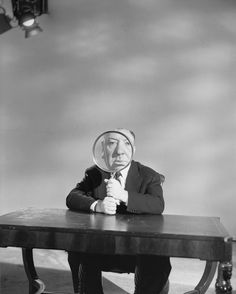 """""""Alfred Hitchcock plays with a magnifying glass on the set of his television program, 'Alfred Hitchcock Presents' """"   Photographer: Otto Bettmann, Hollywood, Los Angeles, USA, May 1956."""