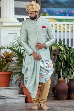 A powder-blue designer Sherwani with floral printed kurta counts to be an exceptional engagement outfit. Also, the mustard pyjama contrasts with powder blue but looks excellent. Mens Indian Wear, Indian Groom Wear, Indian Men Fashion, Indian Man, Groom Fashion, Fashion Suits, Men's Fashion, Dress Fashion, Sherwani Groom