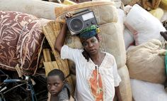 A Burundian refugee woman carries a radio as she rests with her belongings on the shores of Lake Tanganyika in Kagunga village in Kigoma region in western Tanzania, while waiting for MV Liemba to transport them to Kigoma township, May 18, 2015. Burundi's embattled President Pierre Nkurunziza sacked his defense and foreign ministers on Monday, five days after surviving an attempted coup by generals opposed to his bid for a third...
