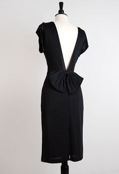 """Lasting Impression dress    Price: $62.00    Very chic vintage 1980s slinky little black dress. I love the backless design especially since it's finished off with a large bow! It's like saying """"I'm a sweet and cute vixen!"""" Front has cowl detail at top and draping in the front."""