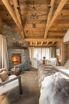 An absolutely gorgeous rustic bedroom with a fireplace. I love that the area rug covers most of the room and the hardwood floor.
