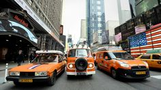 """UNITED STATES, New York : Part of a caravan of 22 orange vehicles begin a 15,600-mile (25,105 kilometers), 80-day, 14-country """"Oranje Trophy"""" tour on March 25, 2014 from New York's Times Square to Rio De Janeiro to promote the Netherlands' national soccer team ahead of the 2014 FIFA World Cup soccer championship in Brazil. The Dutch group will drive first to the west coast of the US before heading south through Mexico, Central and South America. AFP PHOTO/Stan HONDA"""