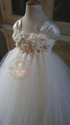 Este vestido está hecho con tul marfil y tiene un top de ganchillo marfil, está adornada con un racimo de flores de seda marfil con centros de perlas y cristal. Este vestido tiene manga marfil con un arco que empareja en la espalda. Es ideal para fotos de retrato, vestido de la