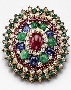 COLOURED STONE AND DIAMOND BROOCH, DAVID WEBB The domed floral motif set in the center with an oval cabochon ruby bordered by round diamonds and by alternating cabochon sapphires and emeralds, further enhanced with round faceted rubies and emeralds, the whole set with 79 round diamonds weighing approximately 6.00 carats, mounted in 18 karat gold, signed David Webb.