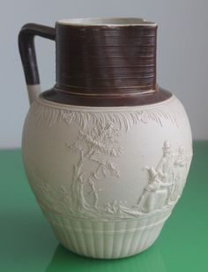 Late 18th Century Turner Stoneware Jug Depicting an Archer 23cm c.1800 This jug comes with some wear to inner lip and otherwise good condition. Handmade with full maker marks & a signature to base. Height measures 23cm approximately. Depicted is an archer teaching a young girl the skill. Pattern varies to all sides. Handle is quite detailed and looks to be in good order. £97