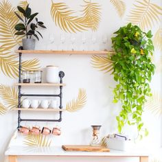 Golden palm frond wall decals in a variety of sizes and shapes placed on a white wall as a palm leaf wallpaper replacement. Each decal features a detailed leaf with vibrant colors.