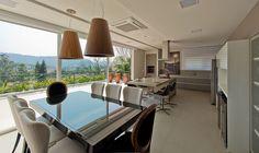 Casa, decoração de casa, casa, com ambientes integrados com tons neutros, como cinza bege, branco e preto. Mesa de jantar, com cadeiras brancas com pendente e luz natural.