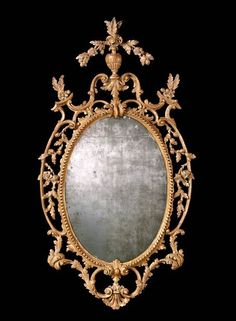 A GEORGE III GILTWOOD MIRROR, CIRCA 1765. The associated oval plate within a guilloche-carved frame with rockwork border, surrounded by pierced C-scroll and foliate and acanthus carvings, surmounted by a flowering vase cresting - Dim: 50 ½ x 27 in. (128 x 68.5 cm.)