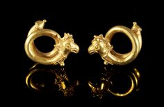 Pair of gold spiral earrings with terminals in the form of a crested griffins head. Cypriot, 475-400 B.C. (Cypro Classical I). Intact.