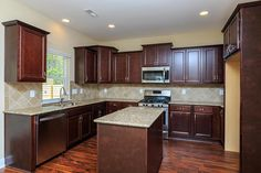 Kitchen with granite countertop, stainless steel appliances and staggered cabinets in the Nelson Craftsman
