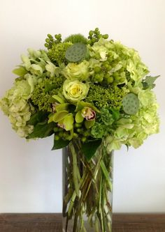 Citrus green bouquet -Tall centerpiece with Super Green roses, green cymbidium orchids, mini green hydrangea, hellebores, green ranunculus, lotus pods, and hypericum berries.  Designed by Green Bouquet Floral Design located in San Francisco Bay Area in Marin County
