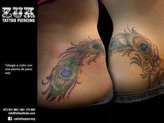 Tatuaje a color con una pluma de pavo real