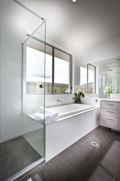 This bright bathroom features large format brown tile flooring and white walls and bath surround. Light wood cabinetry on the vanity adds a layer of detail, as does glass enclosed shower. Bathroom Layout, Modern Bathroom Design, Bathroom Interior Design, Small Bathroom, Bathroom Designs, Bathroom Tubs, Master Bathroom, Bathroom Models, Bathroom With Shower And Bath