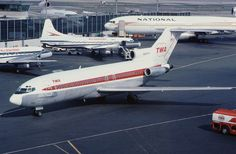 Trans World Airlines (TWA) Boeing 727-31 taxiing at LaGuardia Airport in New York City (a National Airlines McDonnell-Douglas DC-10-10 is parked at the gate in the background)