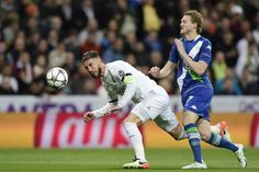 Real Madrid's defender Sergio Ramos vies with Wolfsburg's midfielder Andre Schuerrle during the Champions League quarter-final second leg football match Real Madrid vs Wolfsburg at Santiago Bernabeu stadium in Madrid on April 12, 2016.
