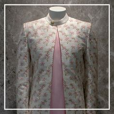 A vibrant combination of lighter tones displaying floral-inspired designs with extreme finesse translates the richness of artwork. A visionary off-white and pink sherwani brings out the essence of a vibrant summer wedding ensemble. Mens Sherwani, Kurta Men, Sherwani Groom, Wedding Sherwani, Boys Kurta, Groom Outfit, Groom Dress, Men Dress, Wedding Dresses Men Indian
