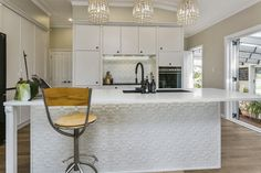 A classic style with modern setting, hand-made doors, lacquer finish, with a black granite bench top running through the storage cabinets and the cooking area, flanked by post like panels.The island contrasts with a white stone bench top, a black granite bowl, black feature tap, and hand crafted legs matching the tall cabinetsPressed steel splash back mirrors the breakfast bar back this combined with villa style handles lends it that country feel