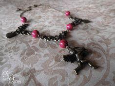 Collier couleur bronze, orné de filigranes floraux, de perles roses, de coeur et de la figure d'un Cupidon.