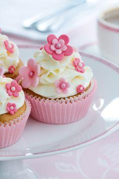 Romantisch: Die Cupcake-Creme wurde hier zartgrün eingefärbt. Eine Zuckerblume sowie kleine weiße Zuckerperlen vervollständigen das kleine Kunstwerk...