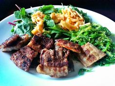 Grilled porkbelly on a bed of kale, spinach and green chard, topped with bamboo shoots in chili sauce with a side of seaweed salad