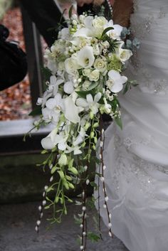 "A glorious winter cascading wedding bouquet of fresh fragrant Rosemary, Athena & Norma Jean Roses, fresh Lily of the Valley, Hydrangeas, ivory Hyacinth, Eucalyptus globes, Euphorbia Fulgens, Mistletoe, Florabunda Rose ""Snowflake"", Champagne Grass, Wax Flower Blossom, Christmas Roses and Stephanotis, Ivy and Crystal Blush Calla Lilies in the trail along with Pussy Willow, Ivory Freesia, Phalaenopsis and Dendrobium Orchids"