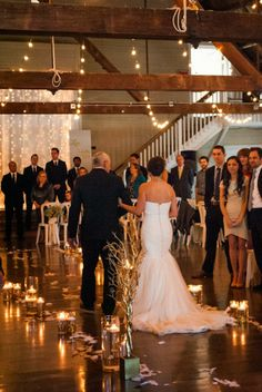 father and bride walking down aisle of feathers and floating candles with twinkle lights