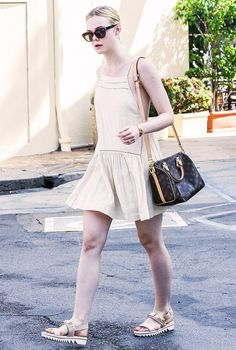 Elle Fanning wears a Free People slip dress, flat sandals, wayfarer sunglasses, and a Louis Vuitton bag