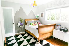 Amanda and Mike's Playful Mix of Modern & AntiqueAt first glance, Declan's bedroom might belong to a whimsical adult, but a closer investigation reveals how 5-year-old-friendly it really is. An IKEA cabinet keeps toys corralled, the IKEA rug is stain-resistant, and the art on display is a fun collection of animal art, family photos, and original pieces by the resident. Bonus: another hand-painted mountain by a talented mom!