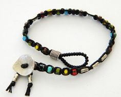 Black Irish waxed linen cord was macrame knotted and combined with Czech glass beads in opaque rainbow shades of red, yellow, blue, green,