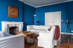 Living con chimenea. Combinación de azul eléctrico, sillones con funda blanca y madera.
