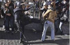 ALBERTO SAIZ (AP) - Un antidisturbios da una patada a un manifestante.