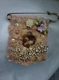 A sweet little vintage inspired unique shabby tattered style kilt brooch. Featuring a lovely victorian fabric image of a little girl surrounded by snippets of vintage lace, pearls, flowers and diamantes. Backed with vintage lace. approx 3X4 with a silver tone kilt pin. Lovely to dress up a sweater, jacket, shawl or dress, for a sweet nostalgic vintage look. Lays flat for reduced shipping cost.