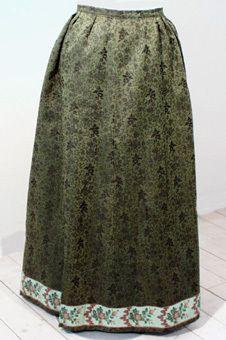 Kjol, allmoge, tillhör dräkt Blm 17102:1-10. Av grön/svart blommigt ylletyg, två våder, blommigt sidenband nertill, lagda veck, fodrad nertill med brun rask. <br /> Från Vallby, Ramdala. <br /> Hör till blekingedräkt (troligen bruddräkt).<br /> Gåva 1977-05-07 av fröken Hedvig Jönsson, Nora.
