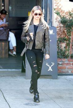 Hailey Baldwin rocks a Saint Laurent sunglasses with a biker jacket over a black T-shirt, RTA jeans, and Balenciaga double-strap boots