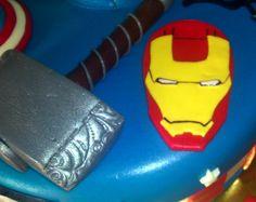 http://dperlas.es/tarta-vengadores/ Seis superhéroes de golpe que se unen a la tarta Spiderman que ya hice. Los Vengadores: El puño de Hulk, la insignia de la Viuda Negra, el arco de Ojo de Halcón, el martillo de Thor, la máscara de Ironman, y el escudo del Capitán América, sobre una tarta base muy americana. El puño de Hulk está esculpido en porexpan y cubierto de fondant. Lo demás es comestible.