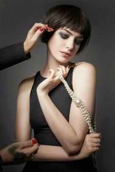 Anne Hathaway mit Pony Kurzhaarfrisur, matte Lippen und Smokey Eyes, schwarzes Kleid, Perlen