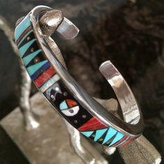 "SALESterling Silver Inlay Cuff Bracelet Authentic Native American hand crafted bracelet featuring hand cut inlaid mosaic design of turquoise, black jade, spiny oyster shell, mother of pearl & silver. Angles & curves in gemstones are unusual for inlaid silver jewelry. The color combination is great & the design is exceptional. Measures 3/8"" wide with an inside end to end measurement of 5 3/4"" plus a nonadjustable gap of 1 7/8"". Stamped sterling-a beautiful showpiece! Jewelry Bracelets"