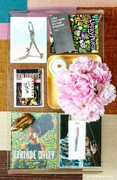 Glass coffee table with gold tray, pink flowers, an assortment of books, notepad with sharpie, and a decorative brass frog // Lena Duhma's New York dressing room