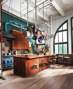 High ceilings and industrial piping are the perfect backdrop for this lovely old vintage range oven and scruffy cabinetry. And just look at those diner style stools...