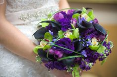 Super lush designed bouquet designed with bear grass, green cymbidium orchids, deep purple lisianthus, and green hanging amaranthys. For the modern bride. Design by Plants N Petals.