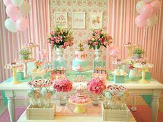 Mesa sem toalha, backdrop esperto com 2 tecidos diferentes e quadros no centro, 2 mesas em 2 níveis diferentes, trilho de mesa em tecido, 3 tipos diferentes de arranjo floral.