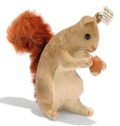 A STEIFF FELT SQUIRREL, (3110,0), brown and white, black boot button eyes, brown stitching, whiskers, reddish brown mohair tail, real acorn between paws and small FF button with white paper tag, circa 1908 --4in. (10cm.) high (slight fading)